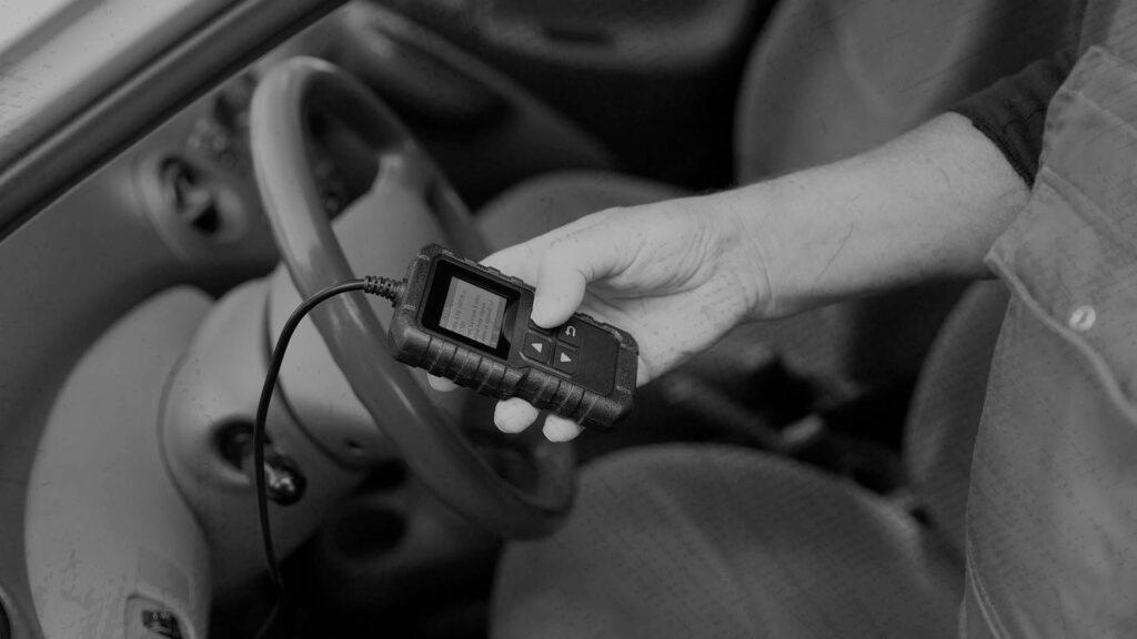 Mecânico utilizando um scanner automotivo em uma oficina